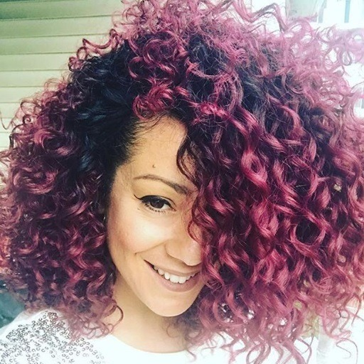 close up shot of woman with medium length red violet natural curls, wearing sparkly jumper