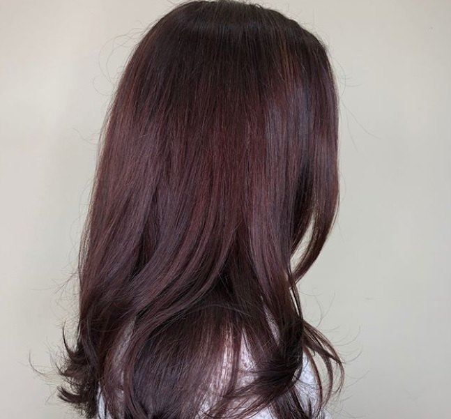close up shot of woman with sleek, layered long red violet hairstyle, wearing white top and posing in a hair salon