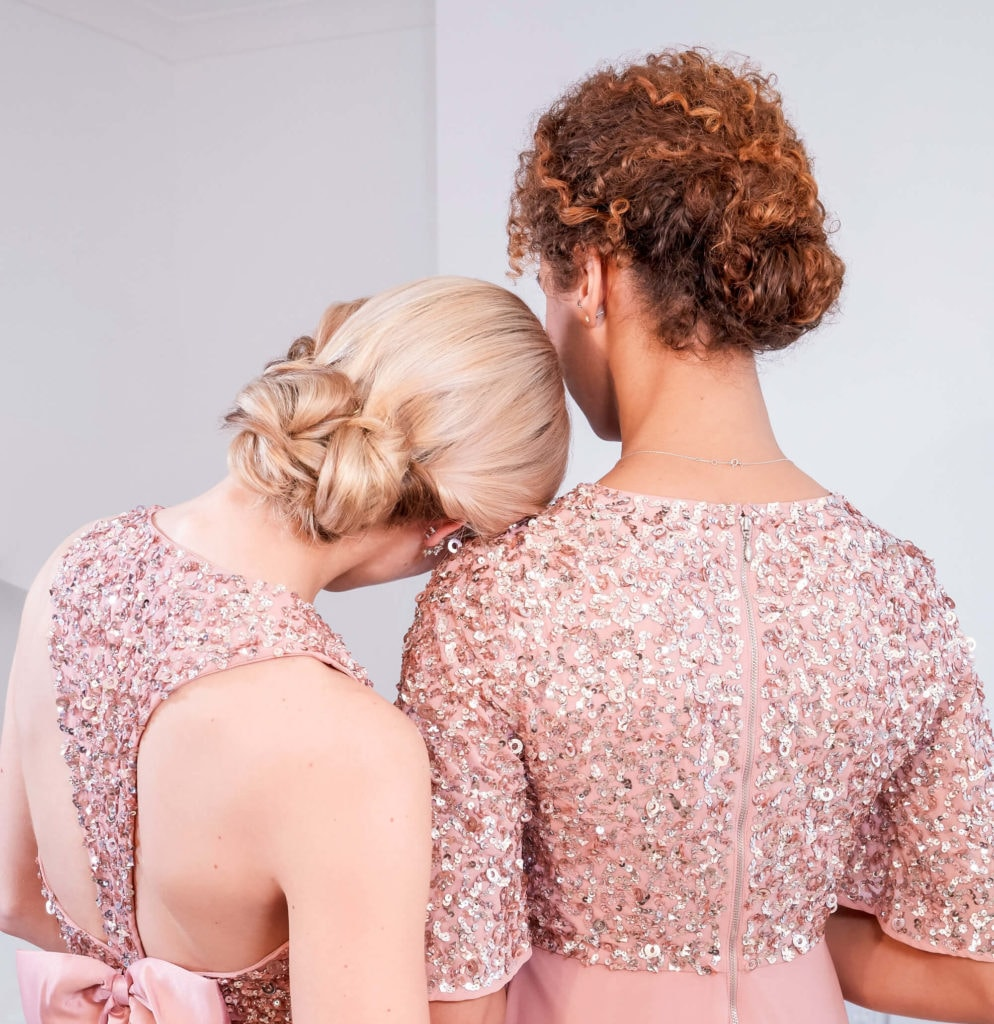 easy natural hairstyles: close up shot of two models with low braided buns, wearing pink formal dresses and posing for an editoral shoot
