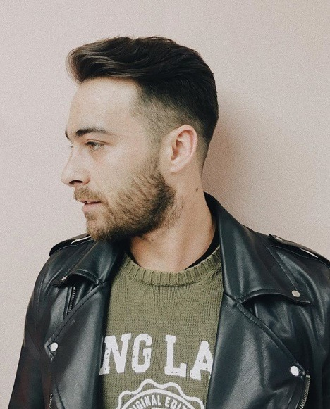 young men haircuts: man with brown hair in a pompadour low fade style with a short beard wearing a green graphic t-shirt with a black leather jacket