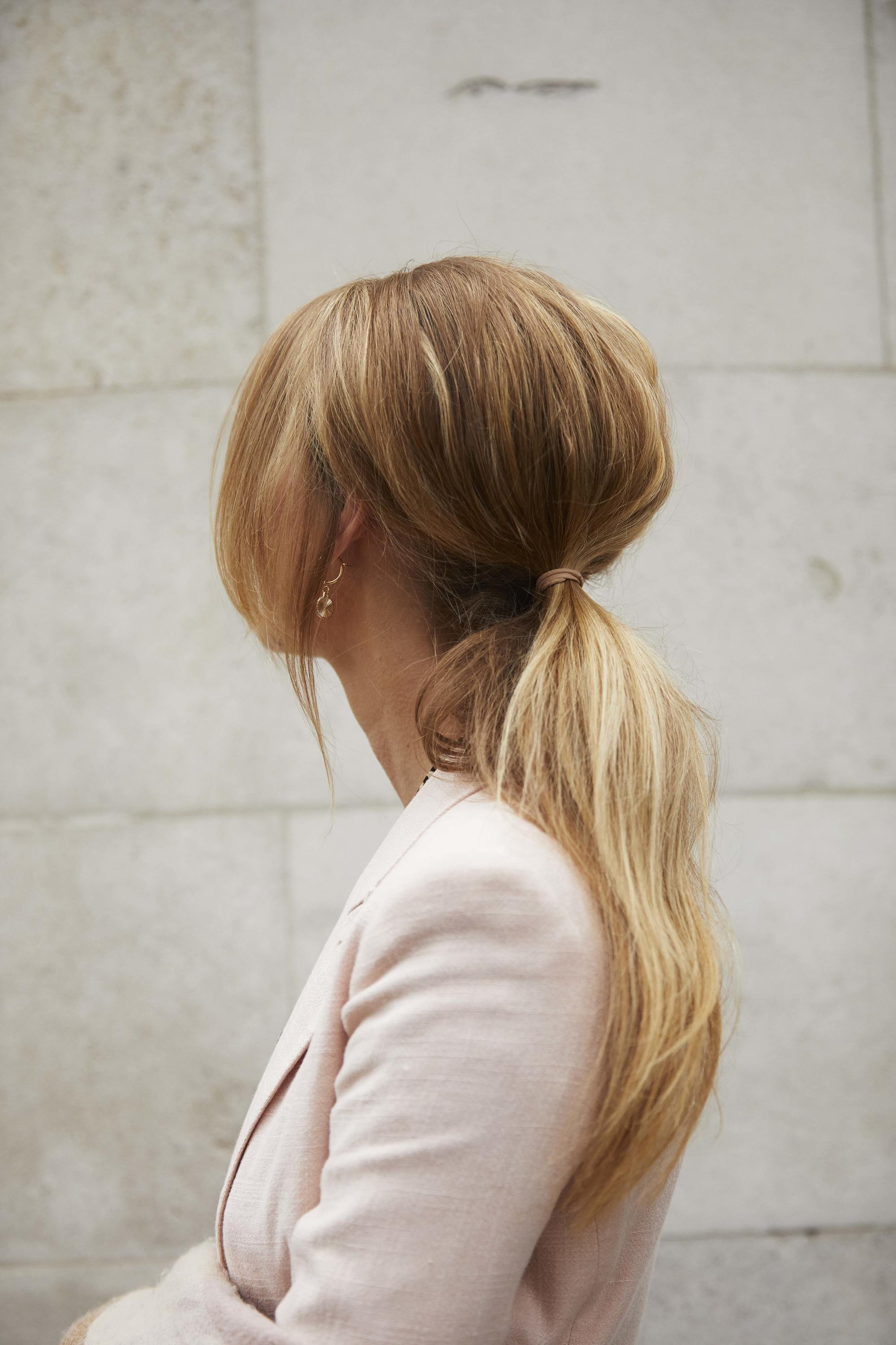 Wedding hairstyles: Woman with long blonde golden hair styled into a bouffant ponytail, wearing a pink suit jacket and posing outside
