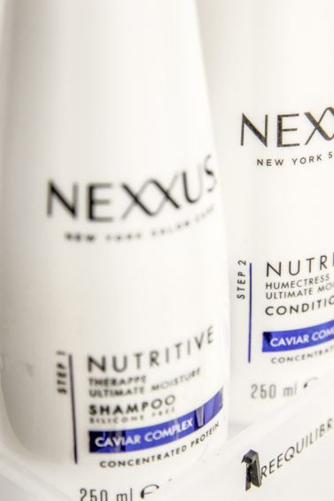 close up shot of the Nexxus Emergencee Protein Shampoo, on an illustrated background