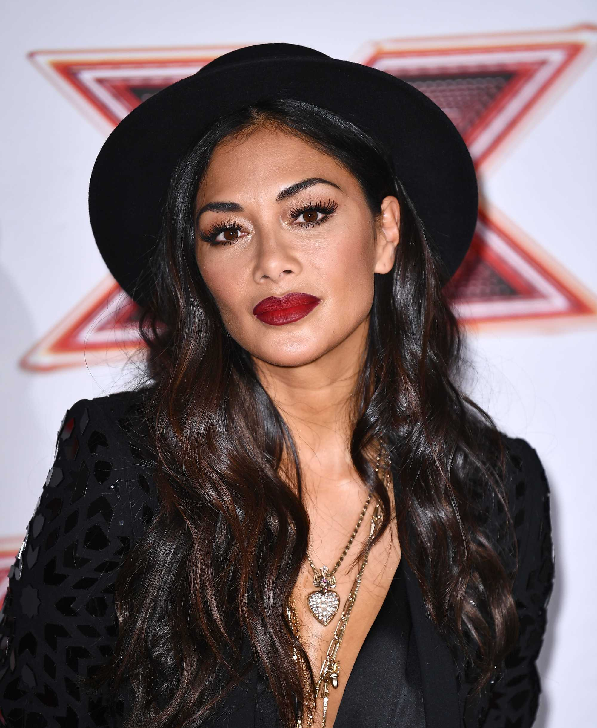 nicole scherzinger at the x factor wearing a black trilby hat with long dark curly hair with lowlights