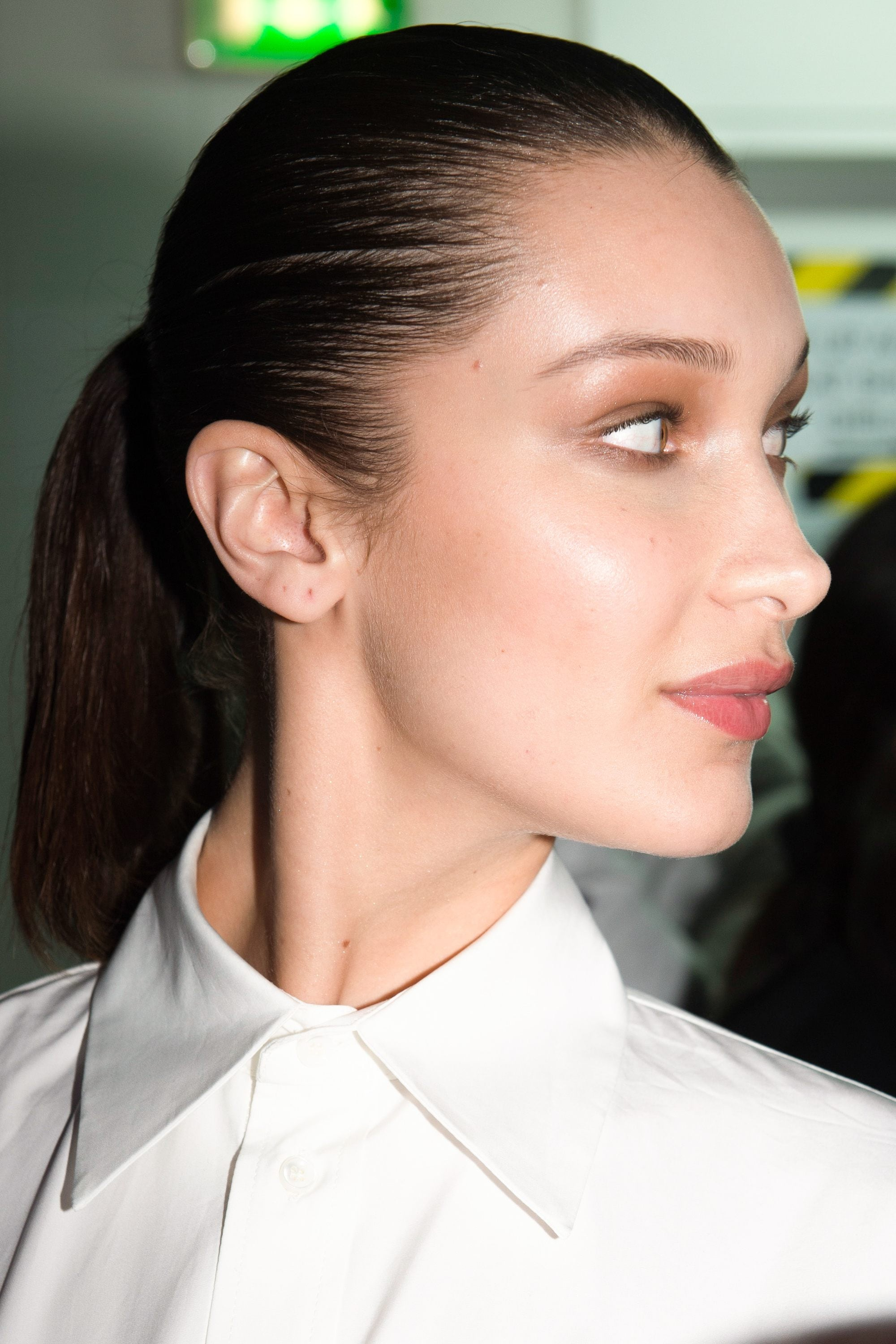 work hairstyles for long hair: side view of bella hadid with straight dark brown hair styles in a smooth ponytail wearing a collared white shirt