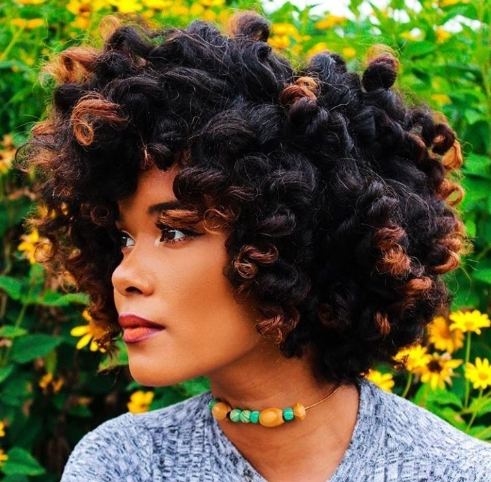 Transitioning hairstyles: Woman with dark brown curly perm rod hair with copper ends, wearing necklace and posing outside