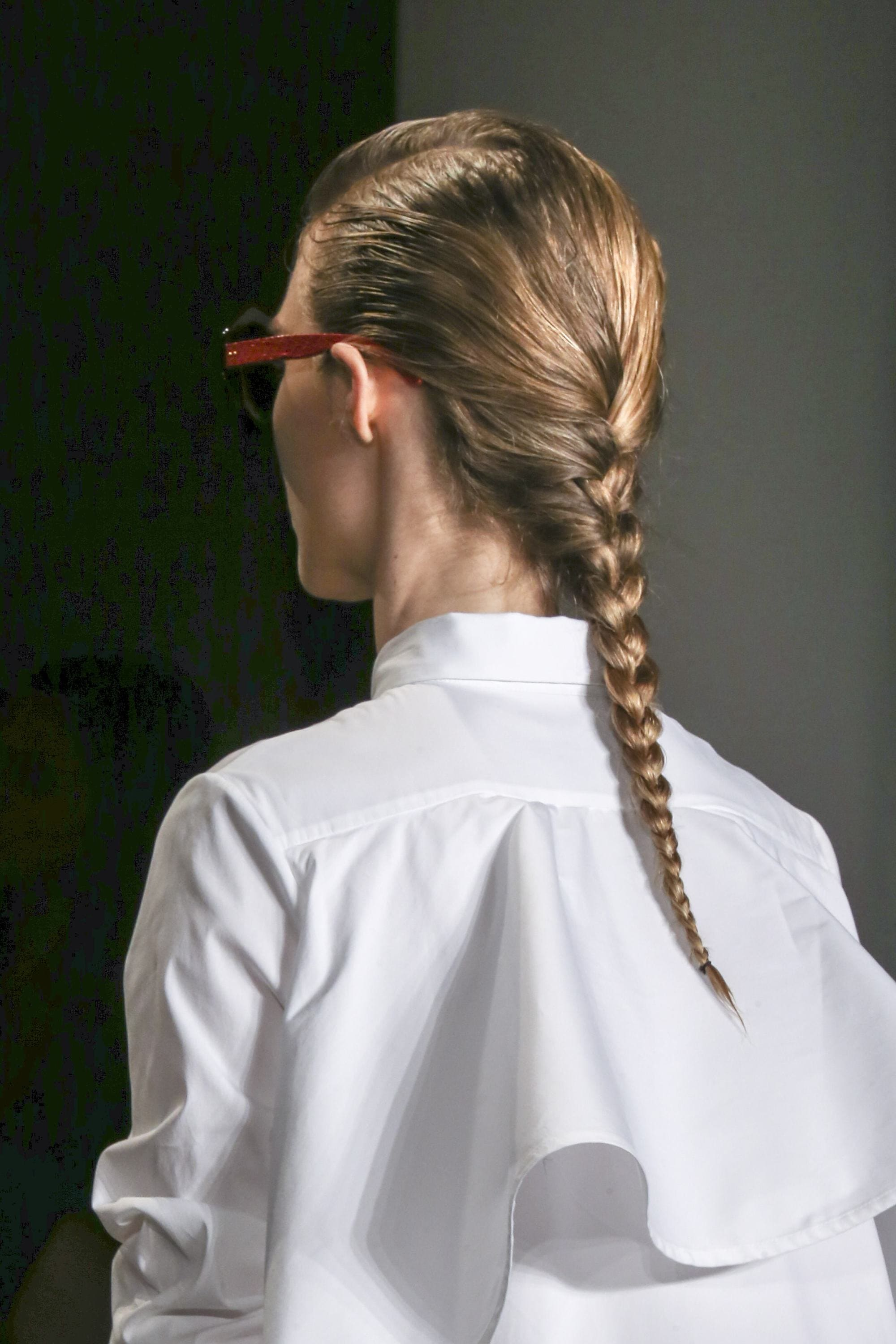 work hairstyles for long hair: back view of model on runway with long dark blonde hair styled in a single braid wearing white collared shirt