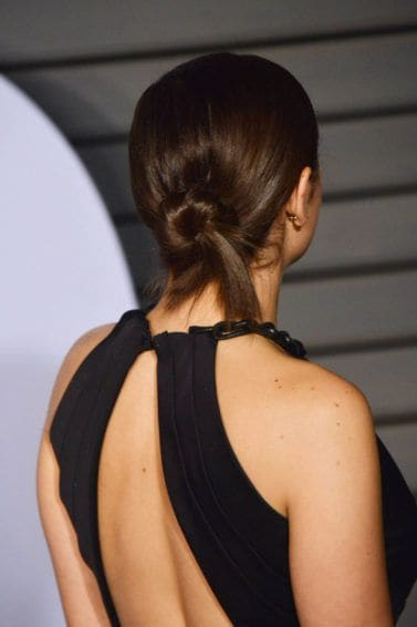 work hairstyles for long hair: back view of charli XCX with medium dark brown hair styled in a low twisted bun on red carpet