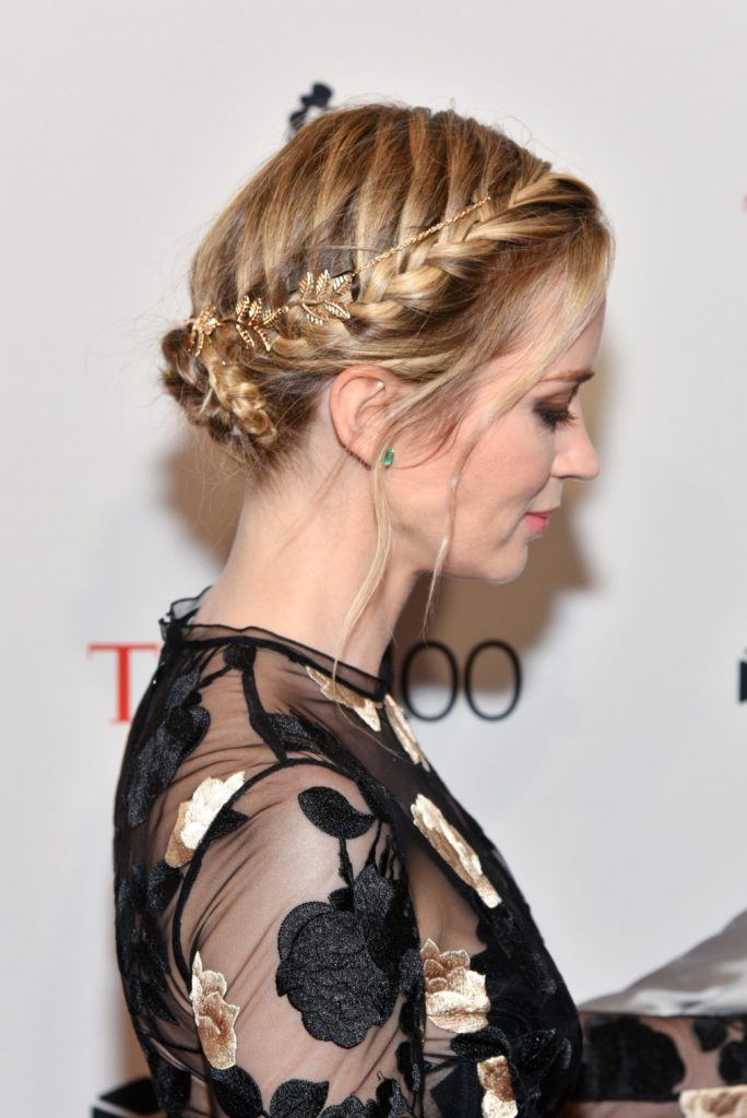work hairstyles for long hair: side view of emily blunt with blonde highlighted hair styled in double dutch braids low bun with wispy strands falling along the hairline wearing a black sheer dress