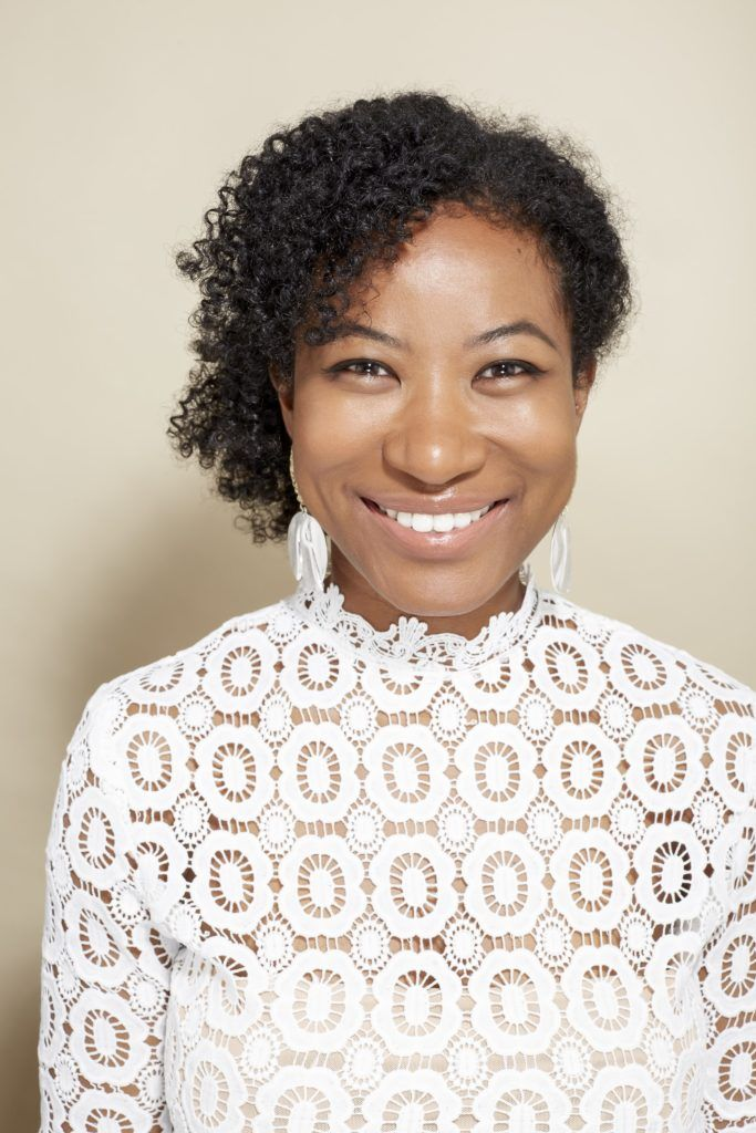 Easy natural hairstyles: Close up shot of a woman with dark brown hair styled into a natural side ponytail, wearing a white lace top and posing in a studio.