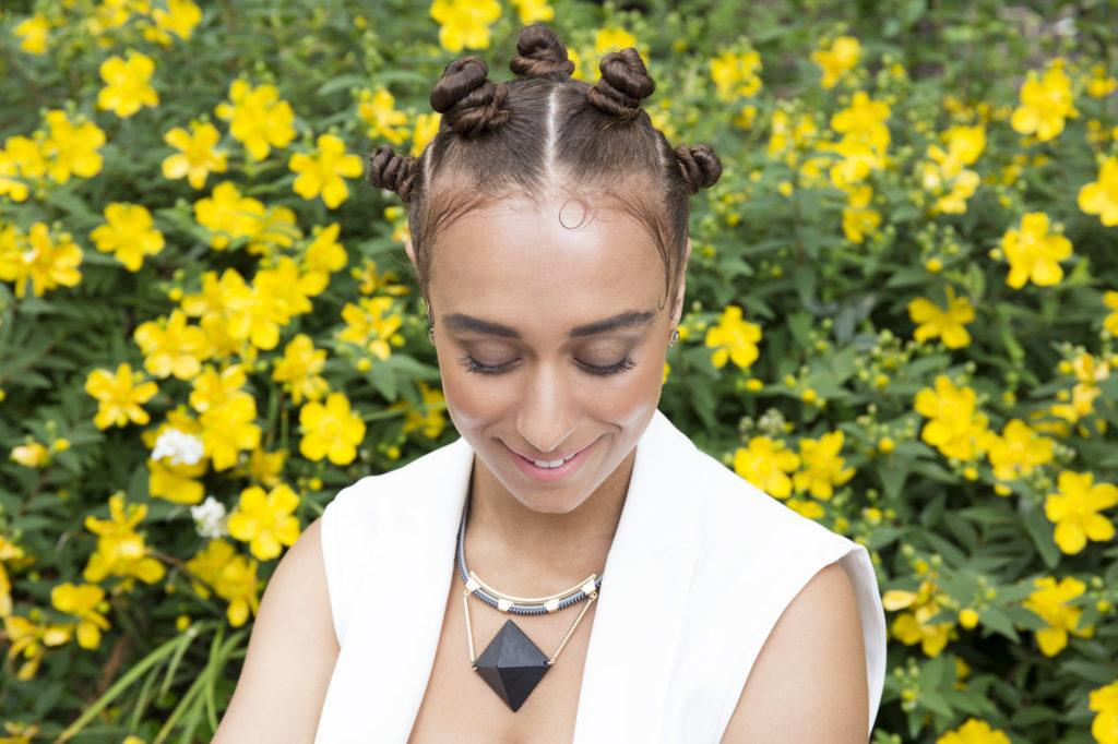 Easy natural hairstyles: close up shot of woman with bantu knots hairstyle, wearing all white and posing next to daffodils.