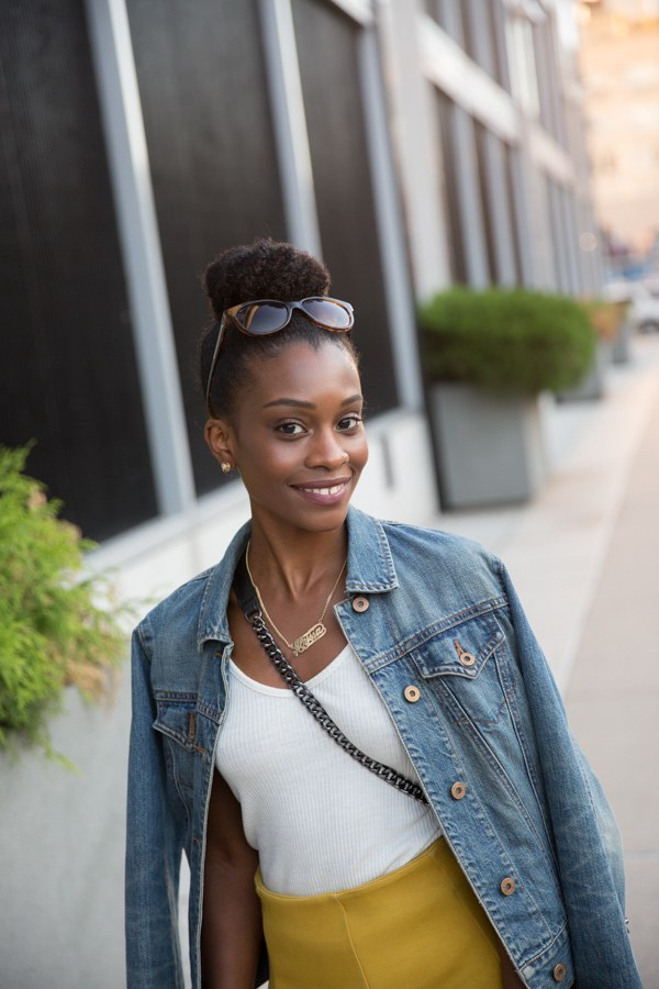 easy natural hairstyles: close up shot of woman on the street with natural hair, with a natural hair styled into a high bun updo, wearing sunglasses and denim