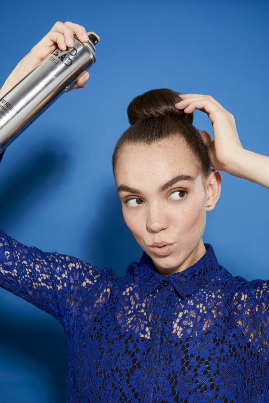 woman with brunette hair in a tight bun spraying it with hairspray, wearing a blue lace outfit