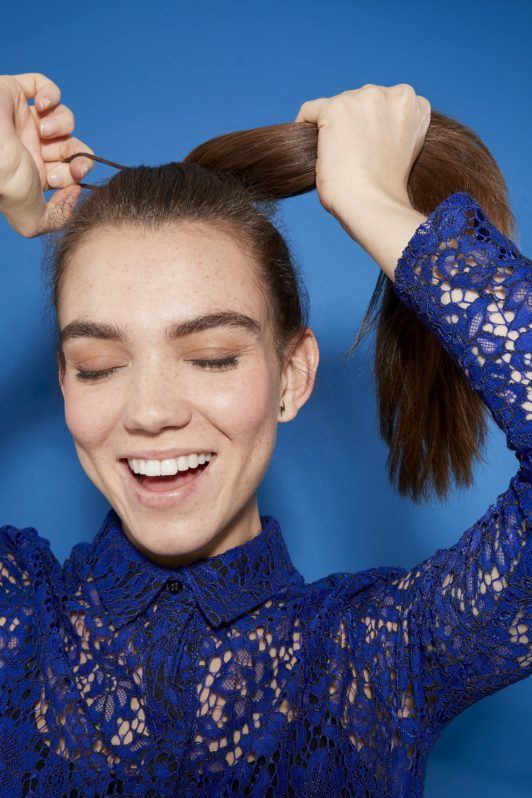 woman with long brunette hair pulling her hair into a ponytail, eyes closed, smiling, wearing a blue lace outfit
