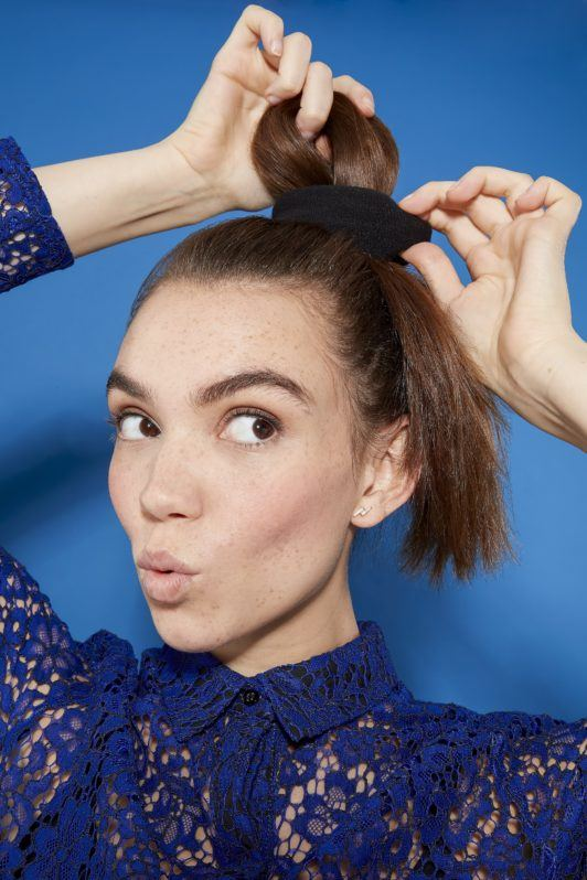 woman with long brunette hair pulling her hair into a ponytail, posing, wearing a blue lace outfit