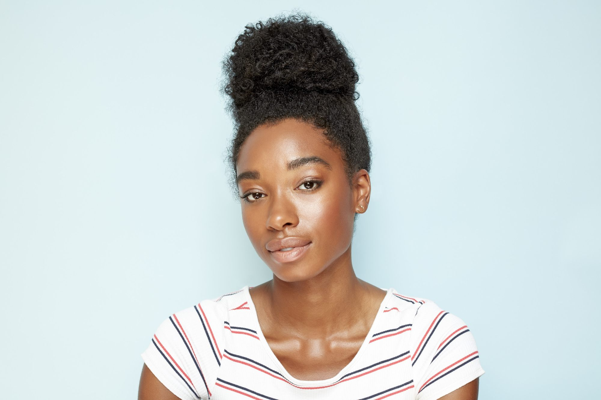 Easy natural hairstyles: Close up shot of a model with dark brown natural hair styled into a high bun, wearing a striped top and posing against a blue background.