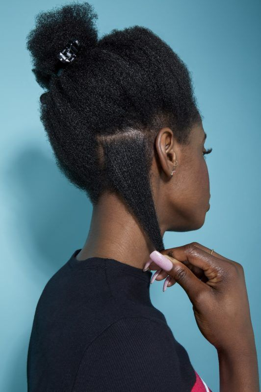 back view of a woman with natural black hair pulling out a small section to style