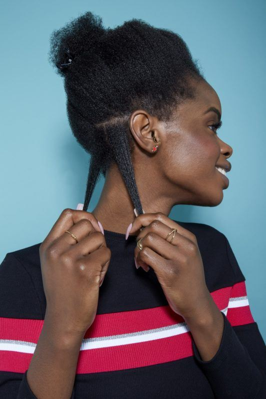 woman with natural black hair pulling down two sections of her hair to style
