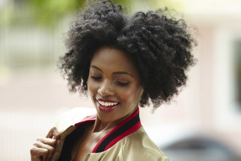 easy natural hairstyles: close up shot of woman with a twist out natural hair, wearing a bomber jacket and posing outside