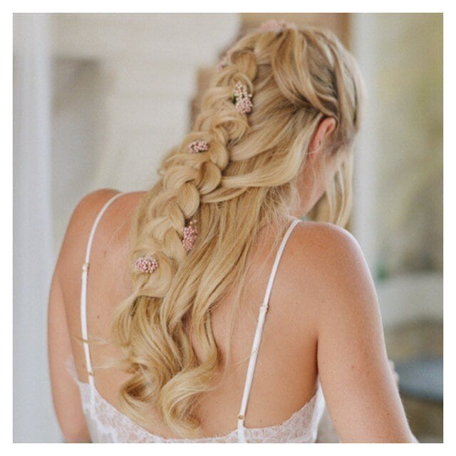 Wedding hairstyles: Woman with golden blonde long hair styled into a half-up, half-down braid with flowers in it, wearing a white wedding dress