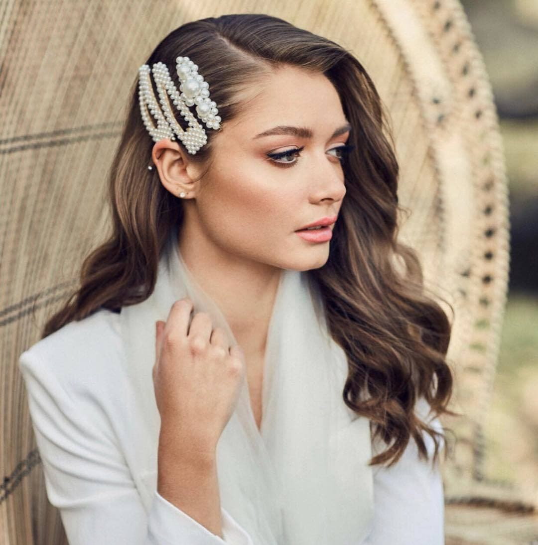 Wedding hairstyles: Woman with long dark brown hair styled into retro glam waves with trendy pearl hair slides
