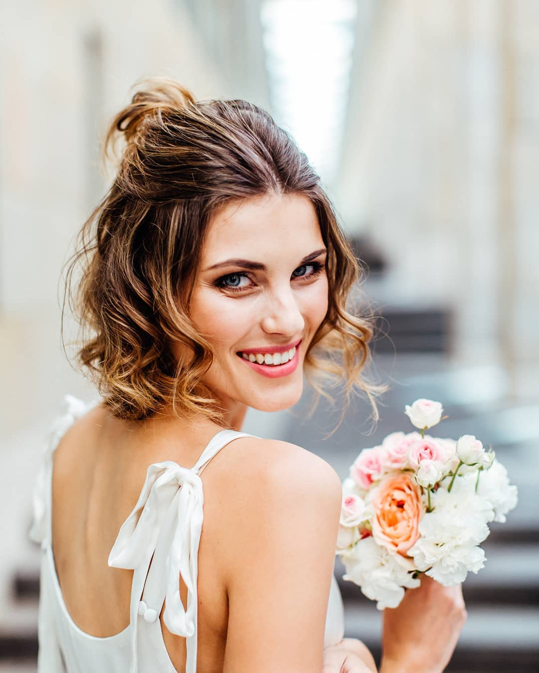 Wedding hairstyles: Woman with half-up, half-down short wavy hair, wearing a white dress and holding flowers