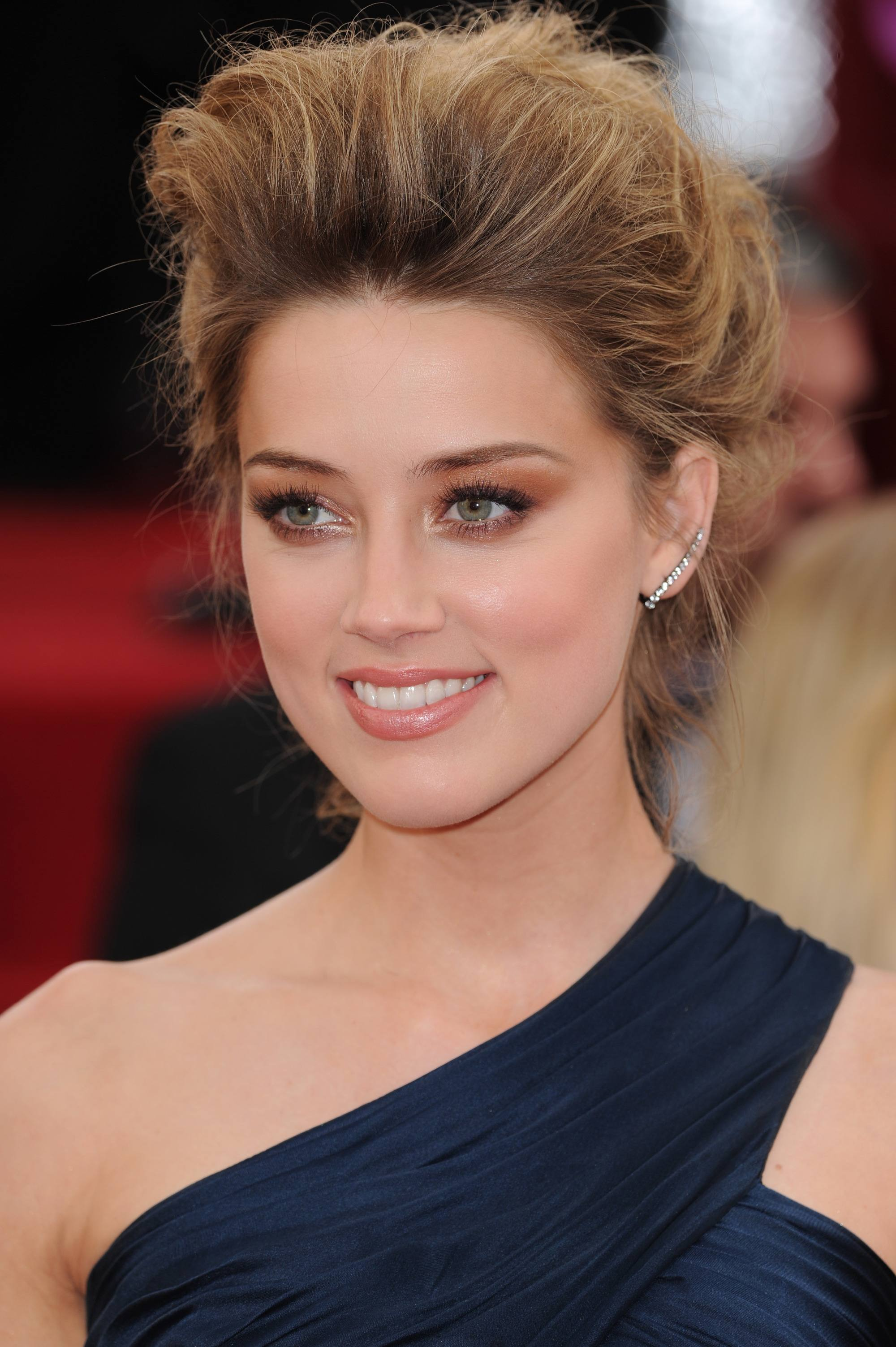 actress amber heard with teased bouffant hair and a one shoulder navy dress on the red carpet