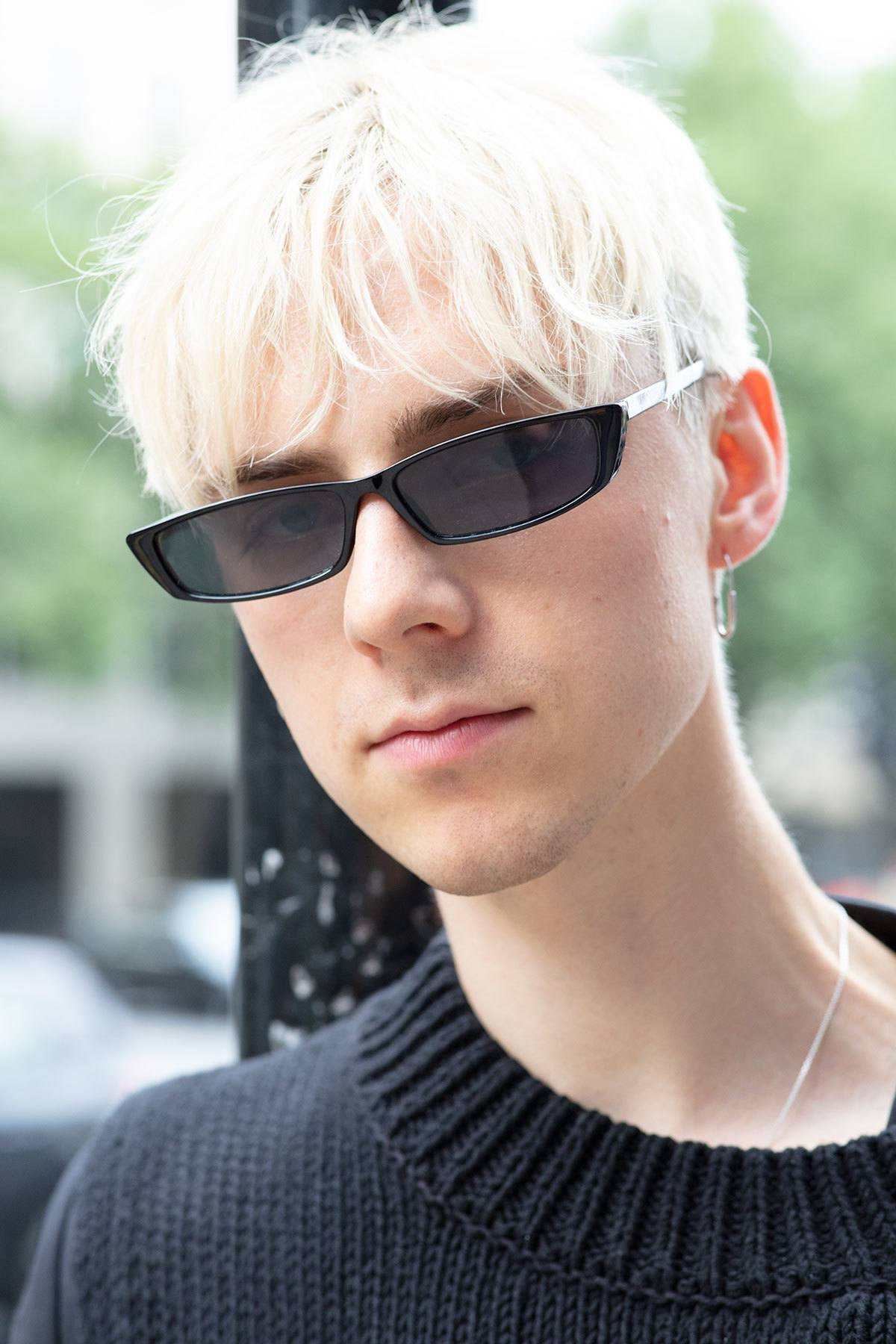 london fashion week men's ss19: close up shot of a man with platinum blonde crop haircut with long, textured fringe, wearing small matrix-style sunglasses and a black crew neck, posing on the street