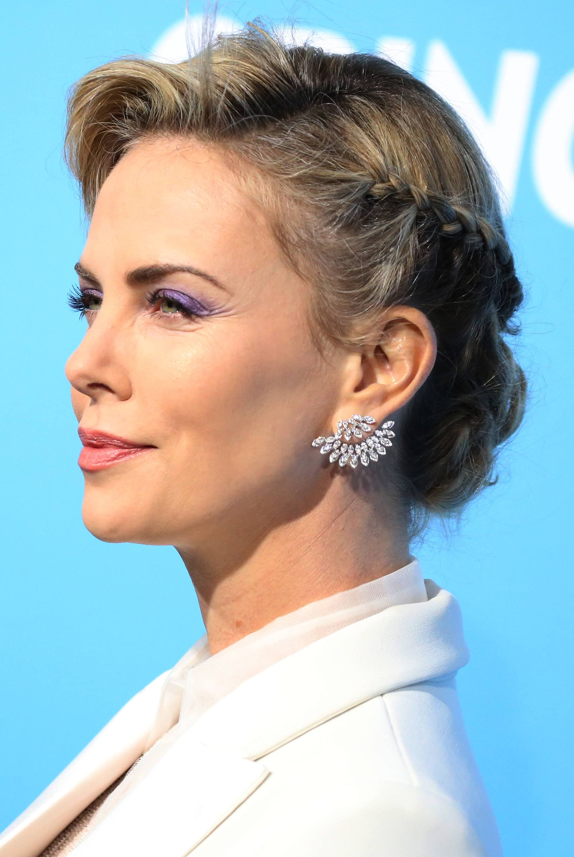 side profile of actress charlize theron on the red carpet with her blonde hair in a low chignon with a side braided detail