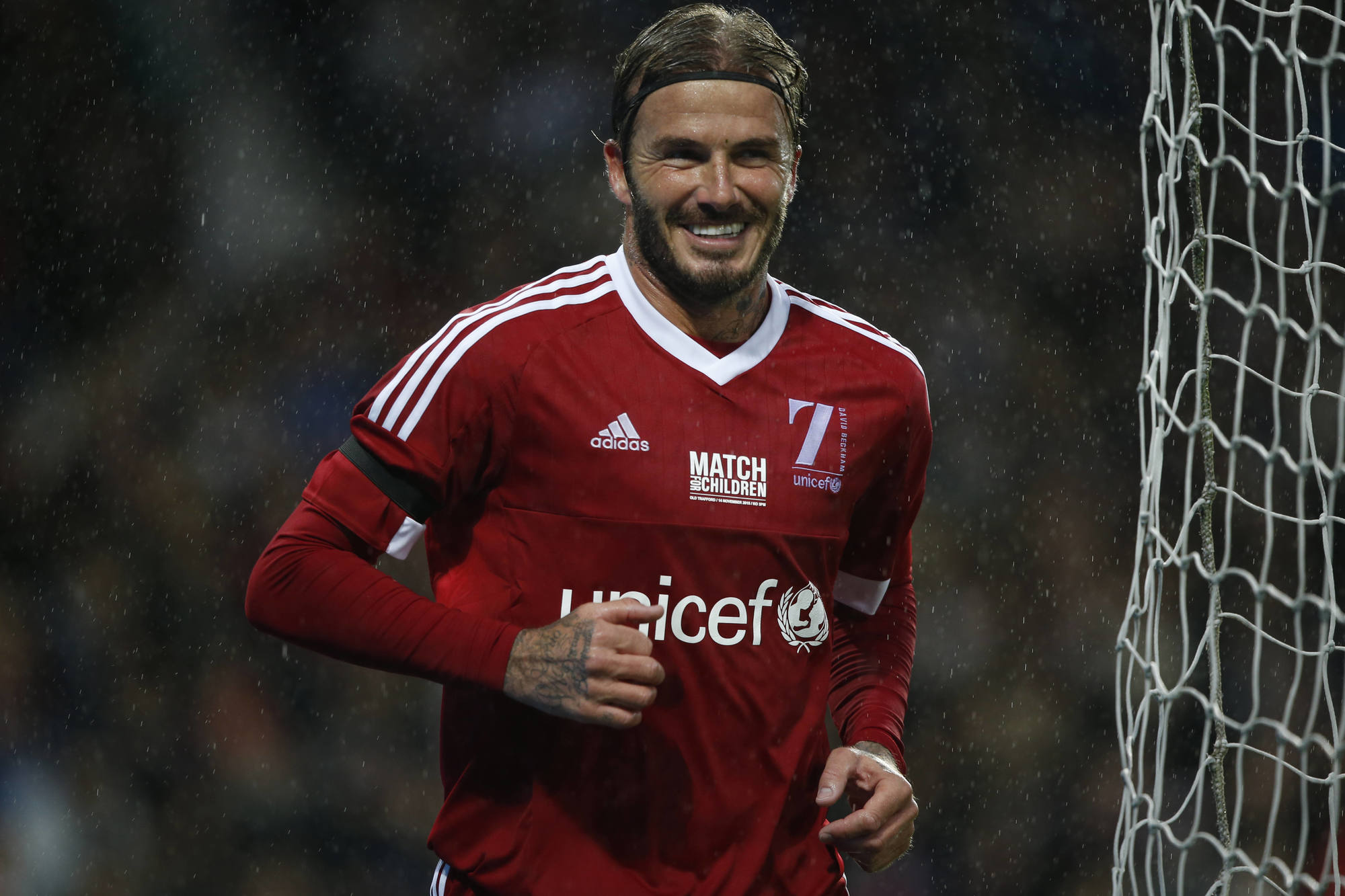 footballer hairstyles: close up shot of david beckham at the unicef charity football match with swept-back hairstyle, wearing red football top and smiling