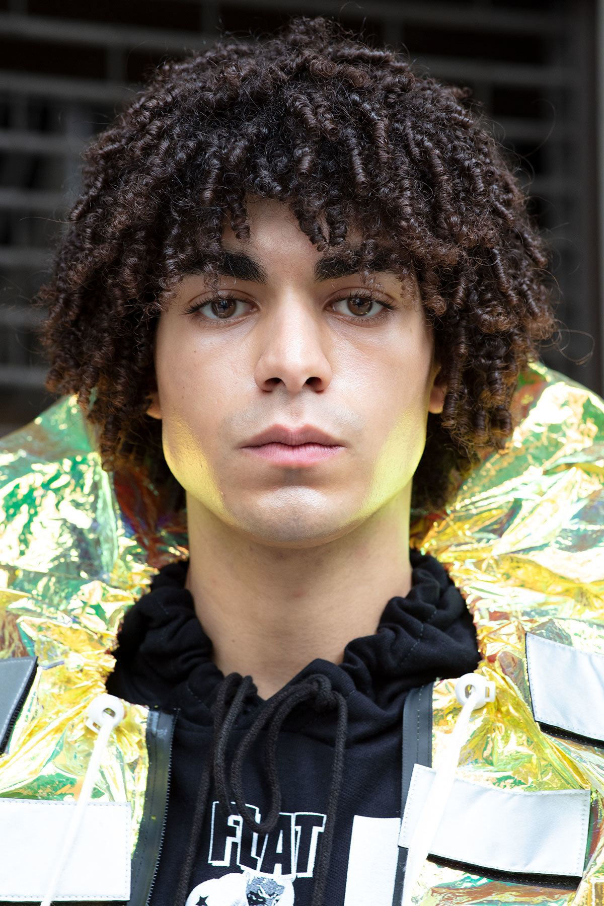 london fashion week men's ss19: close up shot of man with defined ringlet curls, wearing bright raincoat with ruffled neck and posing on the street