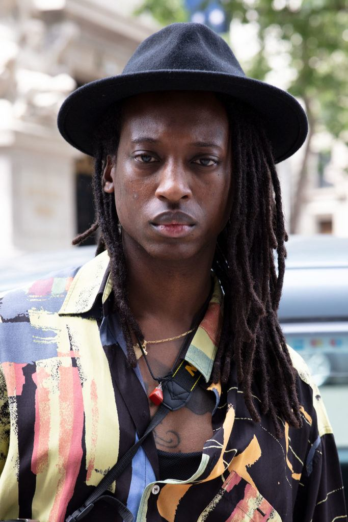 london fashion week men's ss19: close up shot of man with long dreadlocks, wearing fedora hat with patterned silk shirt and some necklaces, posing on the street
