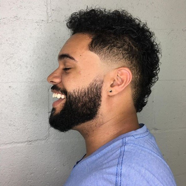 side view of a man with short curly hair cut into a fauxhawk with a beard