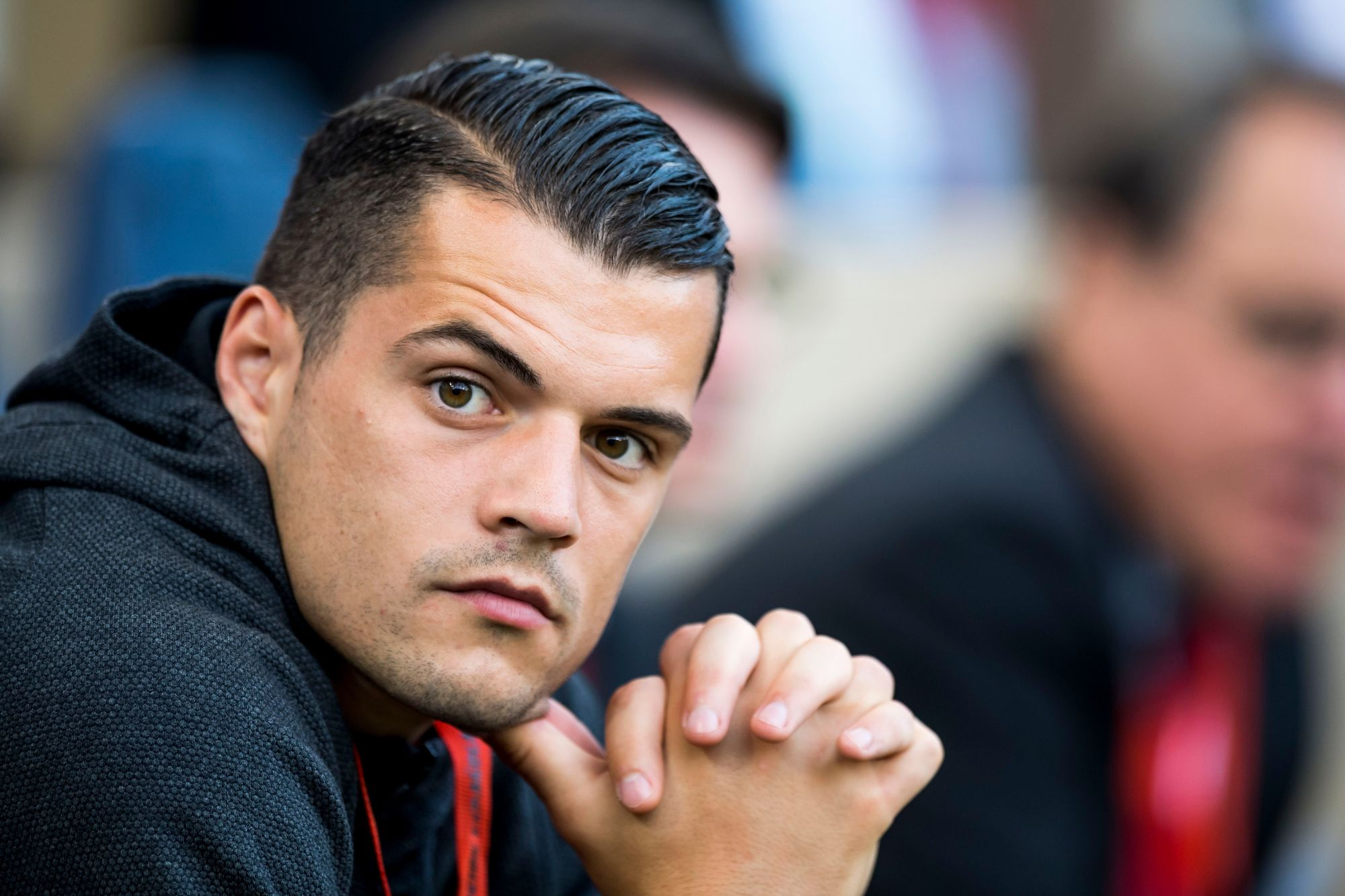 footballer hairstyles: close up shot of swiss profressional footballer granit xhaka with a sleek taper fade hairstyle, waiting for the spain vs switzerland match to start