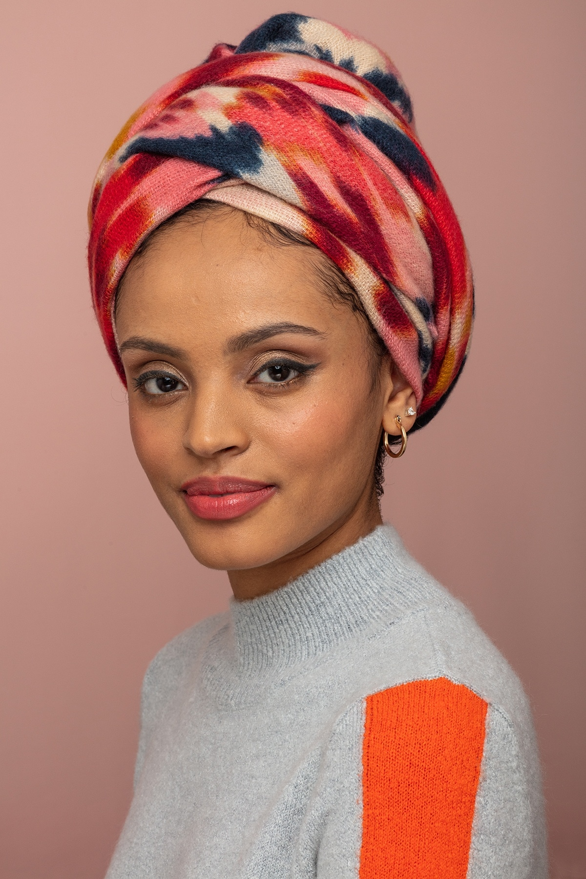 How to wear a headwrap: Woman with pattern headwrap styled in regal style.