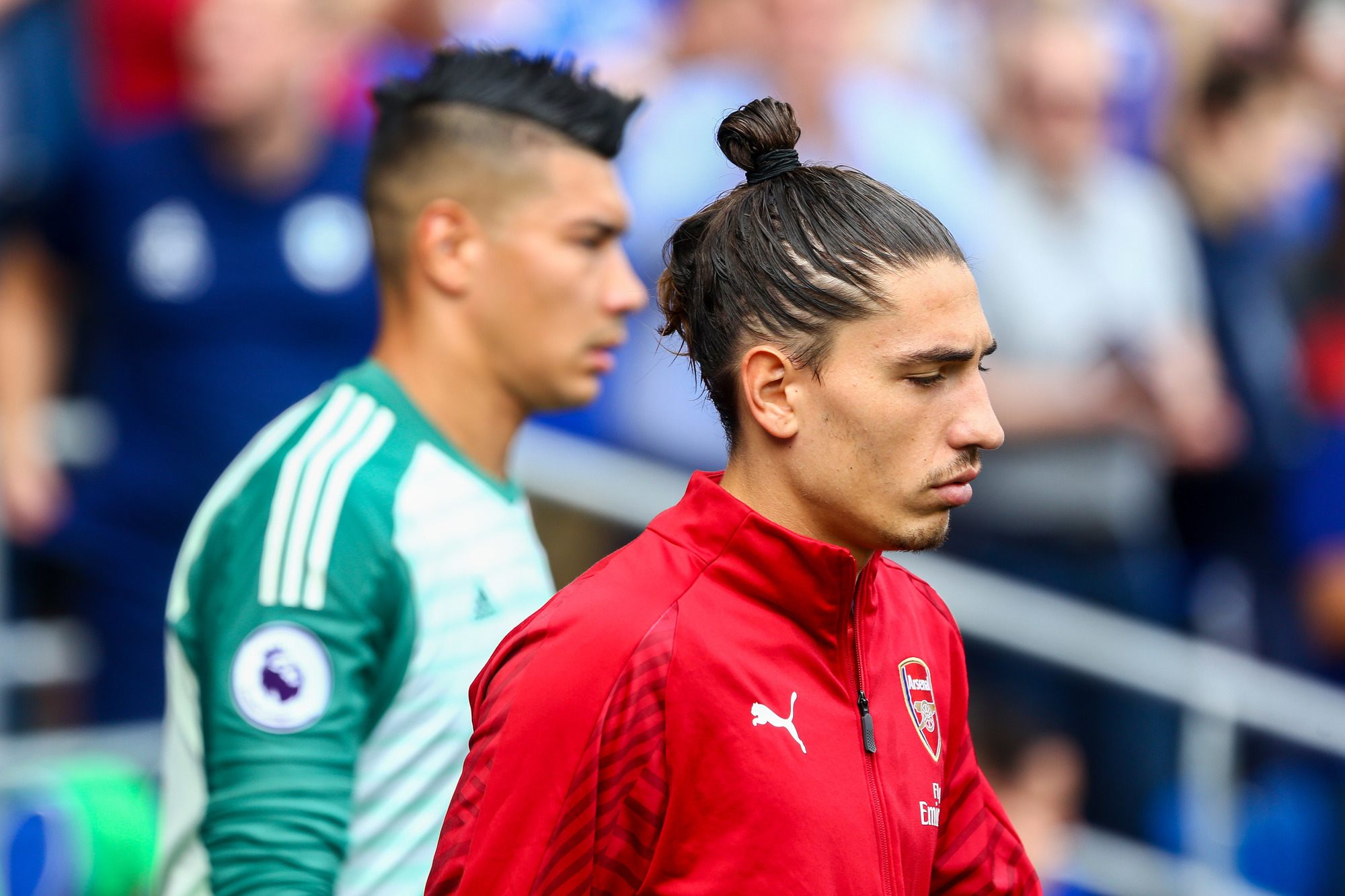 Football hairstyles: Hector Bellerin with brown straight hair in looped man bun wearing red Liverpool football training kit.
