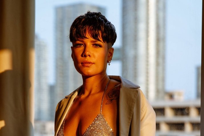 Close up shot of Hasley with a short dark brown bowl cut pixie hairstyle, wearing a silver bikini and posing against a skyline backdrop