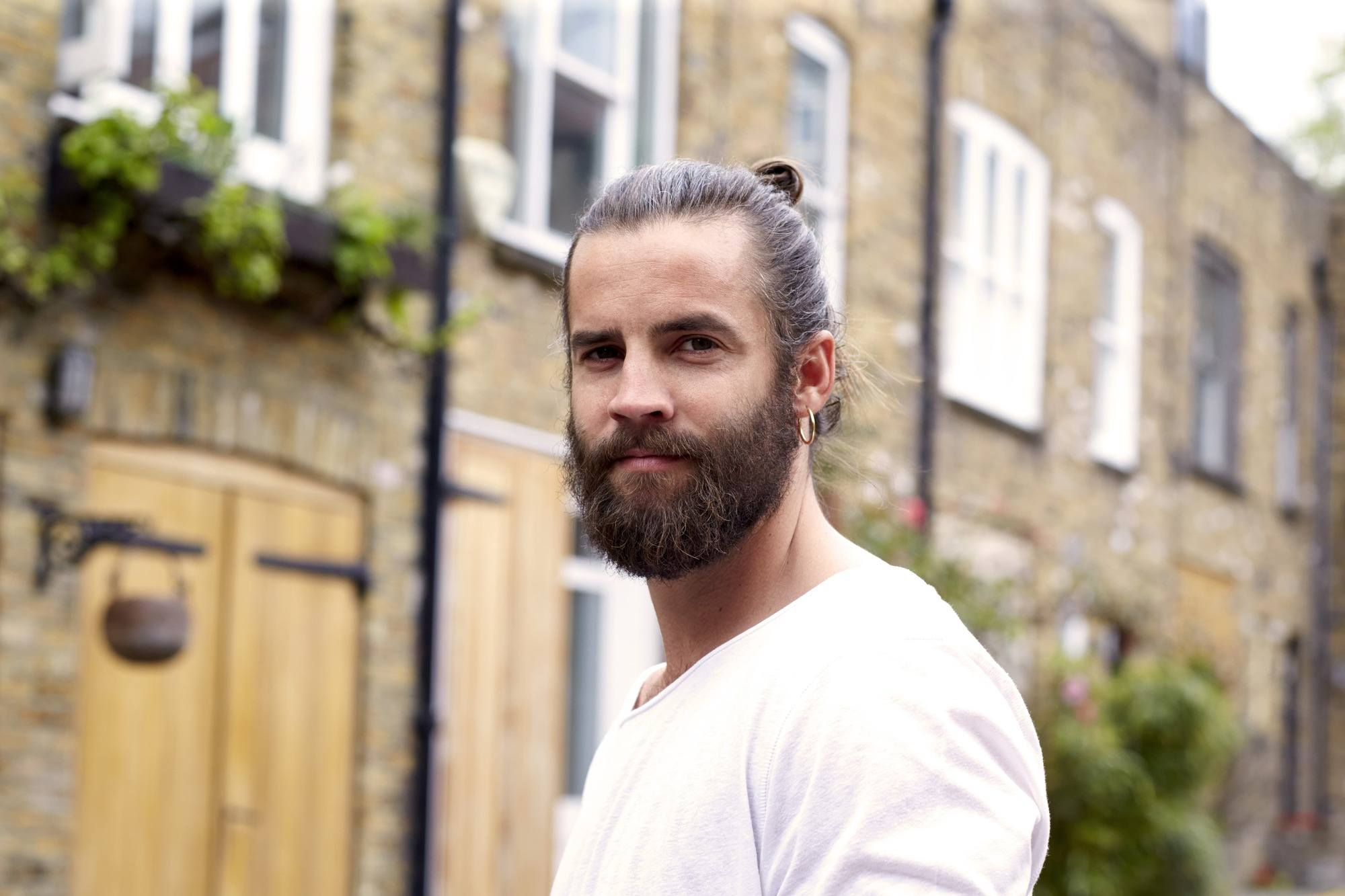 Male grooming: Dark haired man wearing a white T-shirt with man bun and large beard