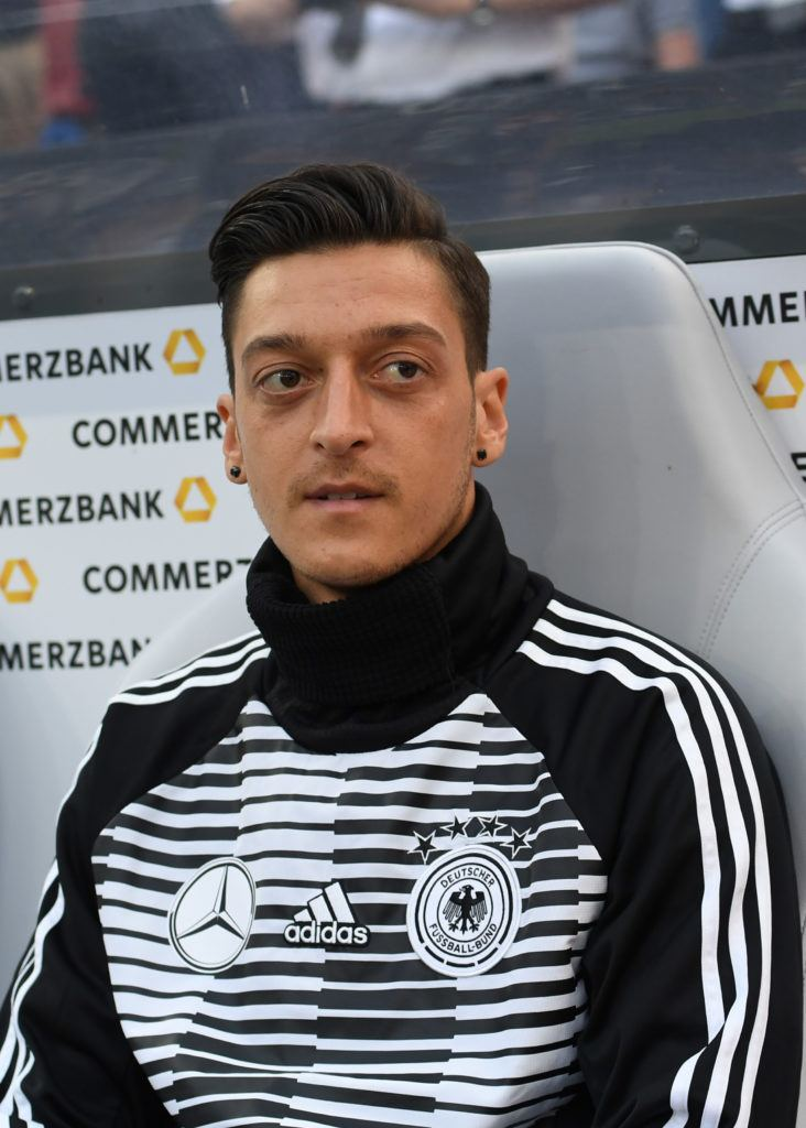 footballers hairstyles: close up shot of german profressional footballer with side parted comb-over hairstyle, wearing black and white jumper, waiting for a match to start