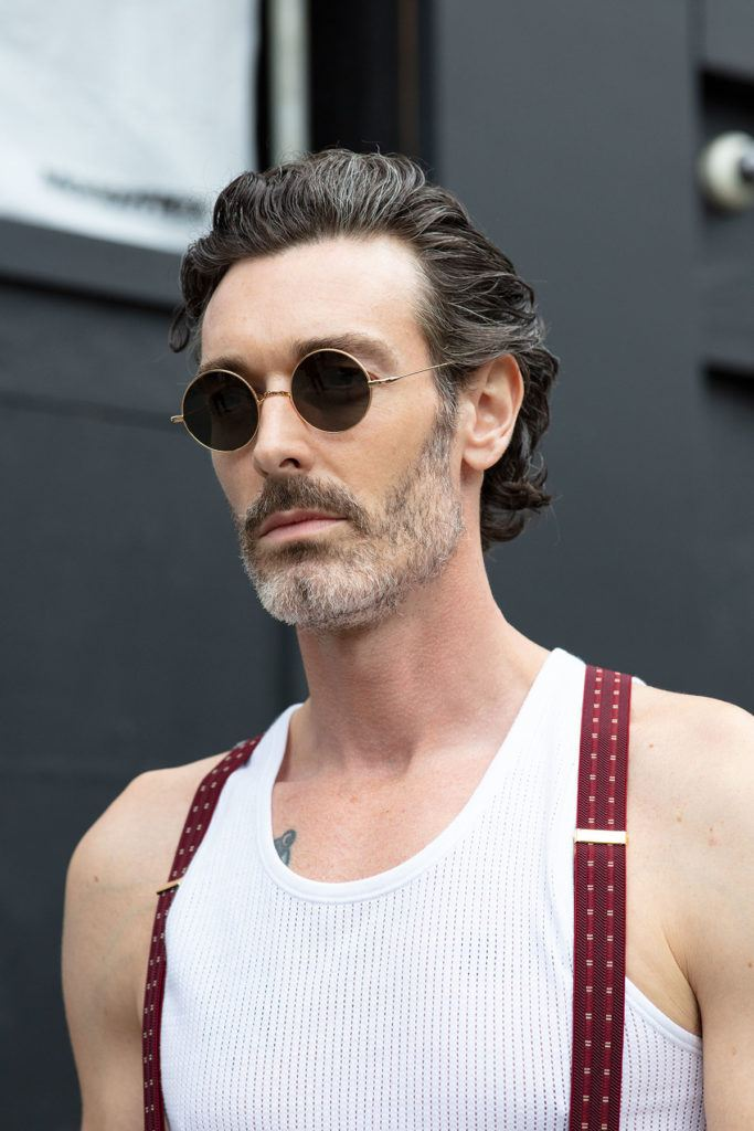 london fashion week men's ss19: close up shot of man with modern bro flow hairstyle and a clean shaven beard, wearing white undershirt with dungarees, wearing ring sunglasses