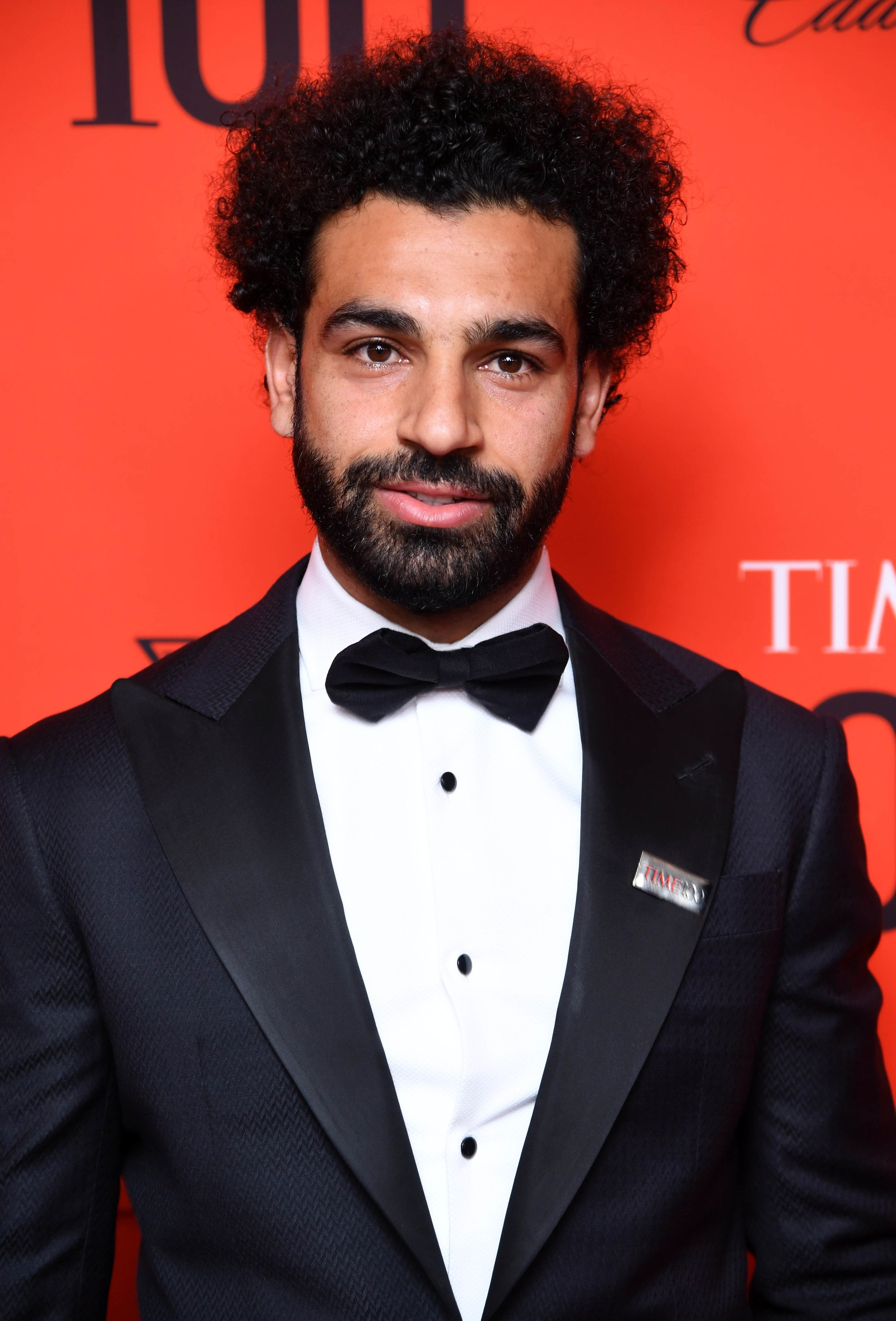 Football hairstyles: Mohamed Salah with naturally curly afro hair wearing a smart suit with bow tie.
