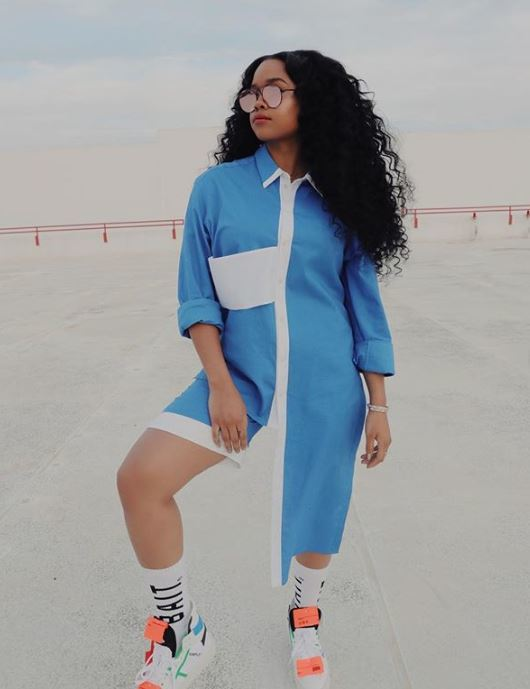 Ones to watch: Singer H.E.R. with long dark brown fluffy curly hair wearing a blue and white jumpsuit and sunglasses.
