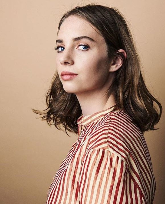Ones to watch: Maya Hawke with shoulder length brown slightly wavy hair with strip top.