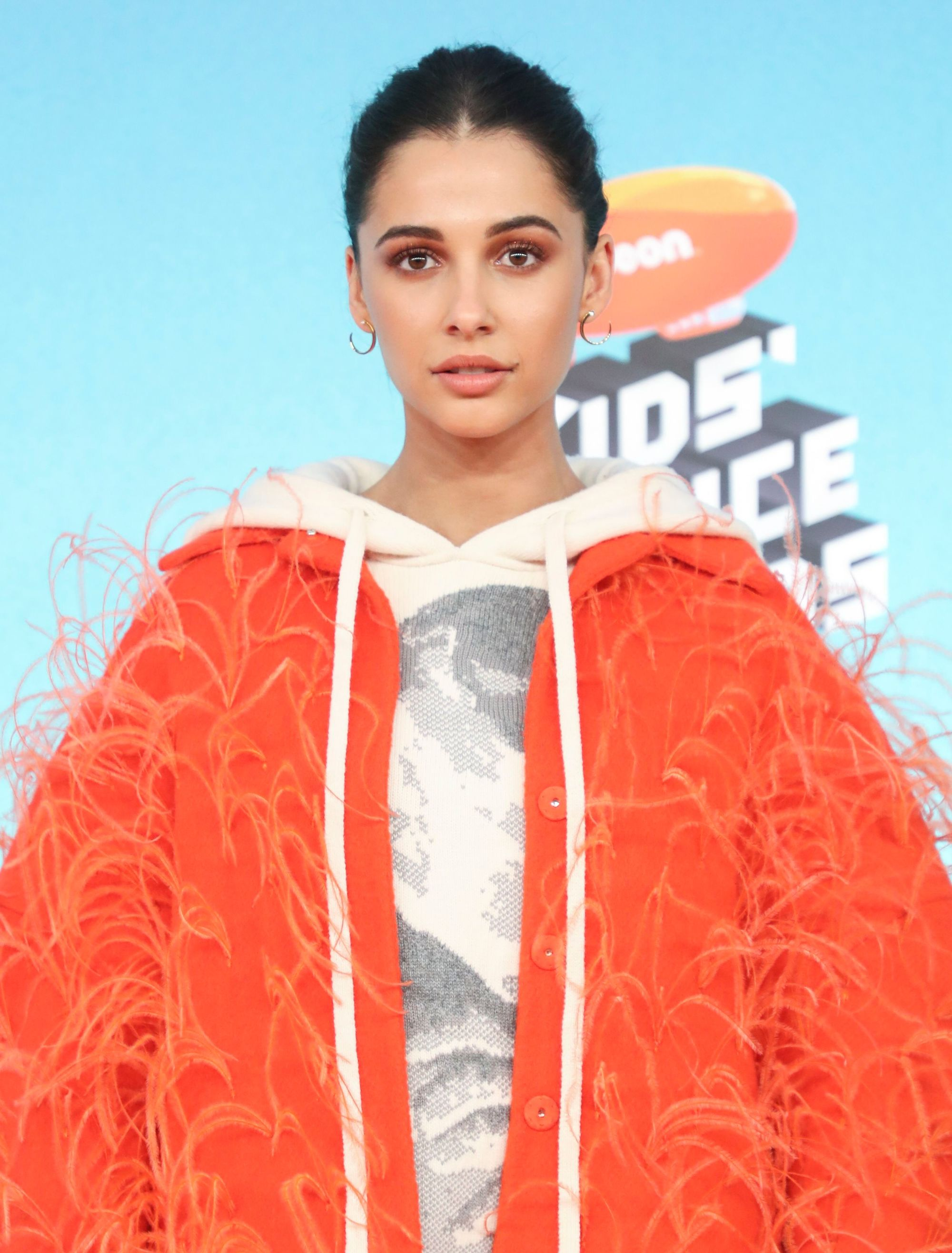 Ones to watch: Naomi Scott with brown hair in updo wearing a bright orange fluffy coat and hoodie.