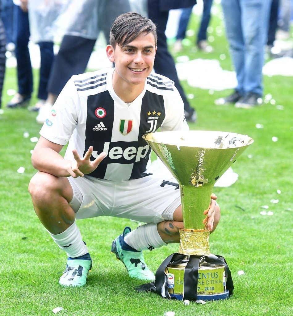 soccer hairstyles: close up shot of argentine profressional footballer paulo bruno exequiel dybala with side swept fringe and undercut, posing next to a trophy on the pitch in italy