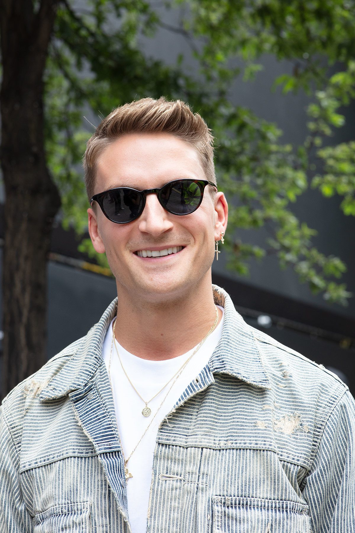 London fashion week men's ss19: close up shot of man with relaxed quiff hairstyle, wearing denim jacket and white shirt, sunglasses and posing on the sreet