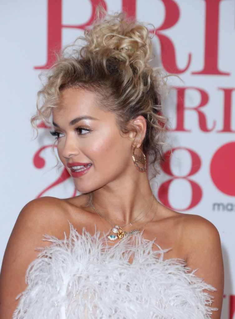 coiffed hair: singer rita ora at the 2018 brit awards with her blonde curly hair in a tinkerbell style top knot
