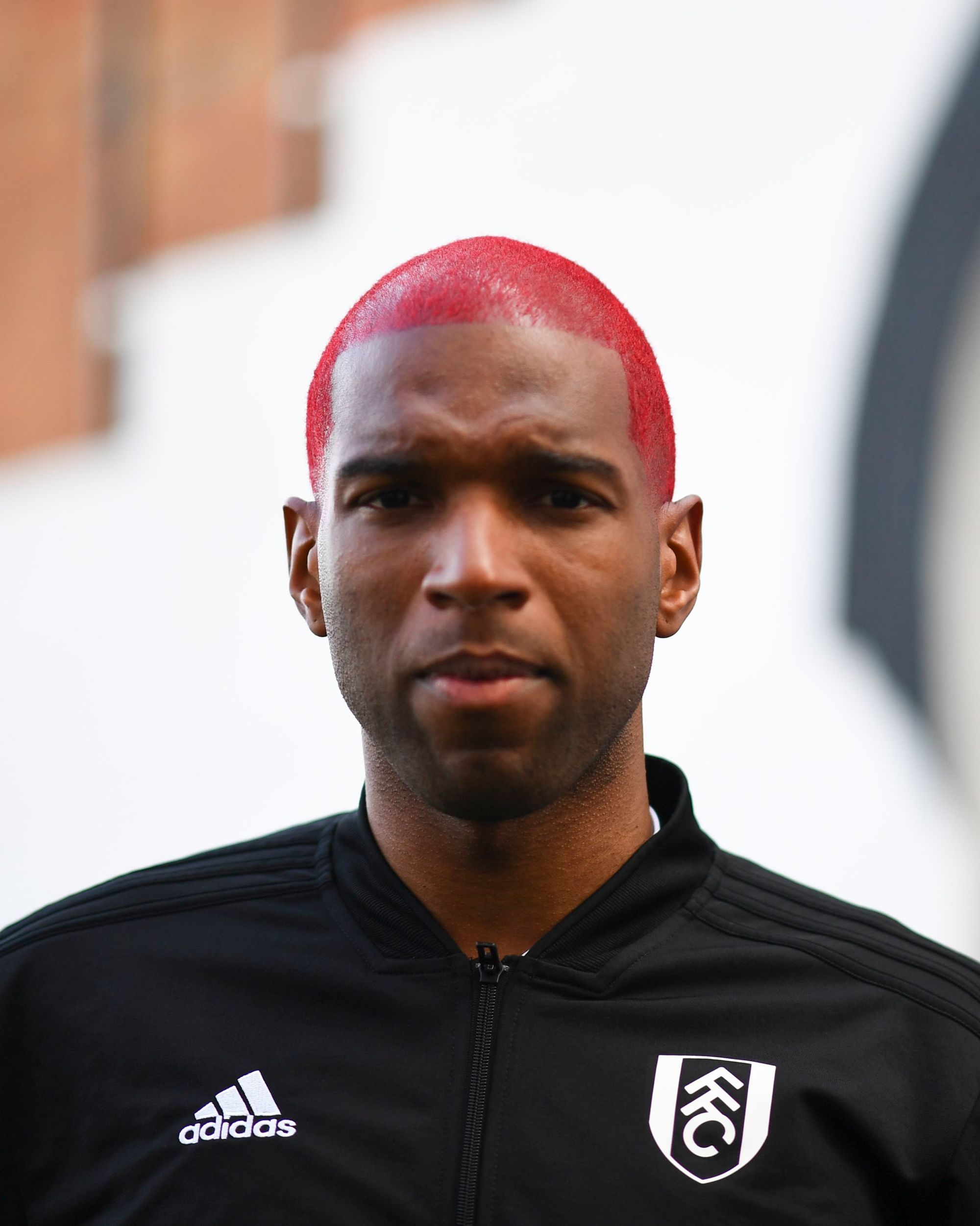 Footballer hairstyles: Ryan Babel with short bright pink hair wearing black football shirt.