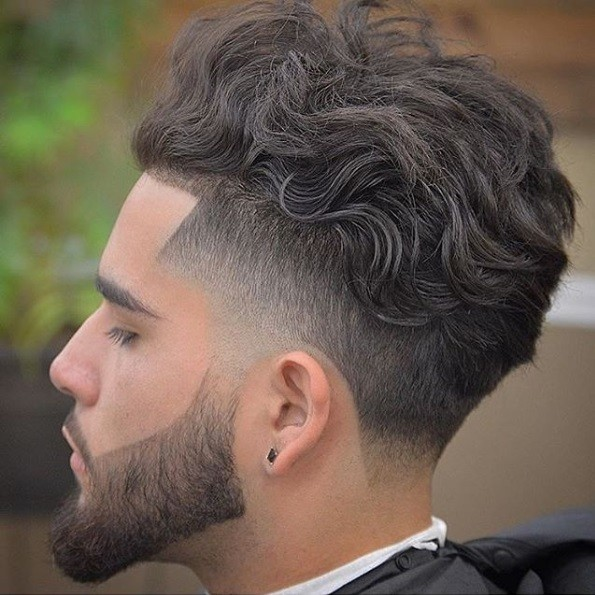 side view of a man with medium brown hair in a curly mohawk style with a fade and shaped beard