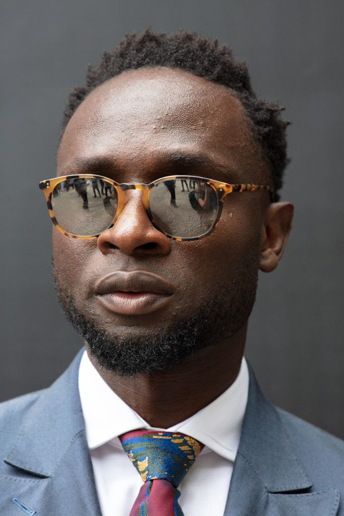 london fashion week men's ss19: close up shot of man with TWA afro and side part hair, with a chin strap style beard, wearing sunglasses and suit and posing on the street