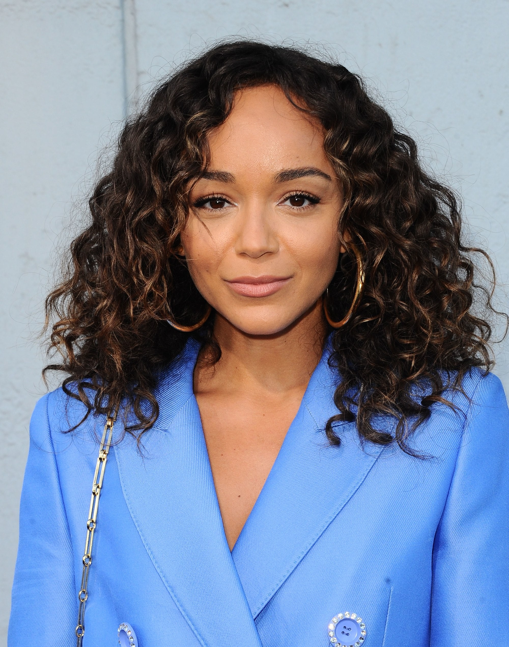 hairstyles for fine curly hair: actress ashley madekwe with a shoulder length curly bob wearing a blue blazer